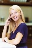 Blondine in der Küche mit Mobiltelefonen Lizenzfreie Stockbilder
