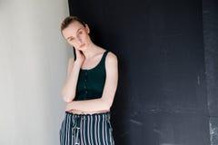 Blondine der modernen Frau wirft auf dem schwarzen Hintergrund des Porträts auf Stockbilder