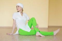 Blondine in der weißen Kleidung nimmt an Yoga teil stockbilder