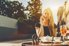 Blondine, die über Smartphone im Café sprechen Stockfoto