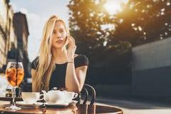 Blondine, die über Smartphone im Café sprechen Stockfotos