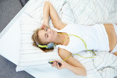 Blondine, die auf Bett während hörende Musik liegen Stockfotografie
