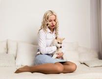 Blondine, die auf einem Sofa mit Welpenschlittenhundhund sitzen Mädchen, das mit einem Hund spielt lizenzfreie stockfotos