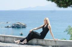 Blondine, die auf Ozean der niedrigen Mauer als Hintergrund sitzen lizenzfreie stockfotografie