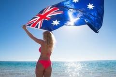 Blondine, die australische Flagge am Strand fliegen Stockbild