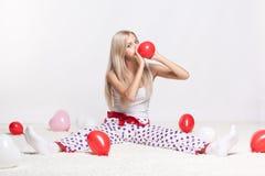 Blondine, die Ballone aufblasen Stockfoto