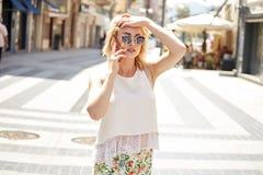 Blondine, die durch Handy sprechen stockbilder
