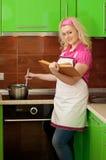 Blondine, die ein Buch liest und Nahrung zubereitet Lizenzfreie Stockbilder