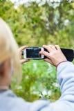 Blondine, die ein Telefon verwenden, machen ein Foto einer Landschaft Lizenzfreie Stockfotos