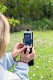 Blondine, die ein Telefon verwenden, machen ein Foto einer Landschaft Stockfotografie