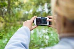 Blondine, die ein Telefon verwenden, machen ein Foto einer Landschaft Lizenzfreies Stockbild