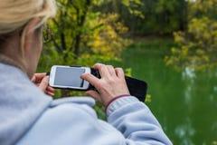 Blondine, die ein Telefon verwenden, machen ein Foto einer Landschaft Stockfotos