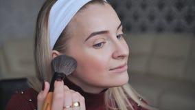 Blondine, die Gesichtspulver an mit einer Bürste anwendet stock video