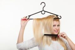 Blondine, die Haar auf Kleiderbügel halten Lizenzfreies Stockfoto