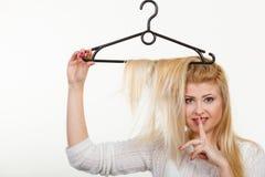 Blondine, die Haar auf Kleiderbügel halten Stockfotografie