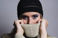 Blondine, die ihr Gesicht mit Rollkragen bedecken Stockfotos