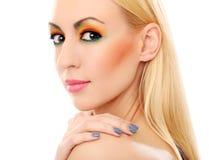 Blondine, die ihren netten farbigen Blick zeigen Stockfoto