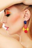 Blondine, die ihren netten farbigen Blick zeigen Stockbilder