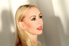 Blondine, die ihren netten farbigen Blick zeigen Stockbild