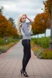 Blondine, die im bunten Herbstpark aufwerfen Lizenzfreies Stockfoto