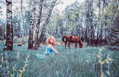Blondine, die im Gras stillstehen Stockbilder