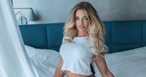 Blondine, die im Hotelzimmer aufwerfen Stockbilder
