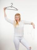 Blondine, die Kleiderbügel halten Stockfoto