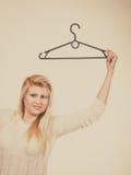 Blondine, die Kleiderbügel halten Lizenzfreie Stockfotografie