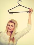 Blondine, die Kleiderbügel halten Lizenzfreies Stockfoto
