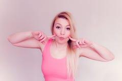 Blondine, die lustiges Gesicht macht Lizenzfreie Stockfotografie