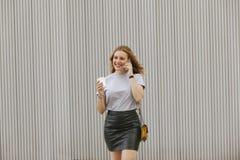 Blondine, die mit ihrem Telefon beim Trinken des Kaffees sprechen Stockfotografie