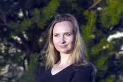 Blondine, die nahe dem Baum im Stadtpark im Sommer, Porträt stehen Lizenzfreie Stockfotos