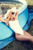 Blondine, die neben einem schmutzigen Planschbecken sich entspannen Schöne junge Frau an einem Pool stockbild