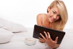 Blondine, die Tablette verwendet Lizenzfreie Stockfotos