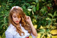Blondine, die unter Baum stehen Stockfotografie
