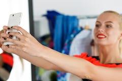 Blondine, die voll nahes Garderobengestell von Kleidung und von MIR stehen Stockfotos