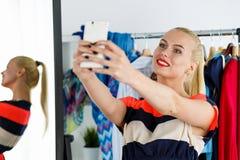 Blondine, die voll nahes Garderobengestell von Kleidung und von MIR stehen Lizenzfreie Stockbilder
