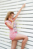 Blondine, die am weißen Plankenhintergrund sich lehnen Stockbild