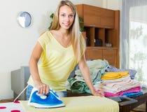 Blondine, die zu Hause bügeln Stockfotografie