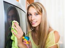 Blondine, die zu Hause Fernsehen säubern Lizenzfreie Stockbilder