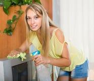 Blondine, die zu Hause Fernsehen säubern Lizenzfreies Stockfoto