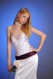 Blondine in einem eleganten weißen Abendkleid mit Weißrose in ihrer Hand Lizenzfreie Stockfotos