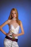 Blondine in einem eleganten weißen Abendkleid mit Weißrose in ihrer Hand Lizenzfreies Stockfoto