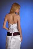 Blondine in einem eleganten weißen Abendkleid steht mit seiner, die zurück in Profil gedreht wird Lizenzfreie Stockfotografie