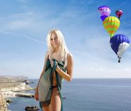Blondine in einem pareo auf Strand mit baloons im Himmel Stockbild