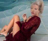 Blondine in einem roten Kleid, mit Fallschirmhintergrund Lizenzfreies Stockfoto