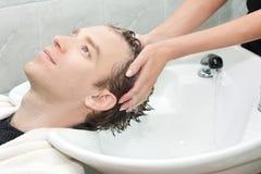 Blondine in einem Salon, der ihrem Haar mit sha gewaschen erhält Stockfotografie