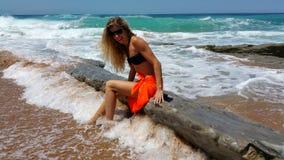Blondine in einem schwarzen Bikini und in der Sonnenbrille und orange pareo auf dem Strand Lizenzfreies Stockfoto