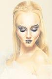 Blondine in einem weißen Kleid mit blauem Make-up Die Schneekönigin Stockfotografie