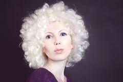 Blondine in einer Perücke sendet einen Kuss Stockfotos